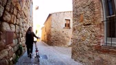 ecotourisme : A girl with long hair walks with a bicycle in the small stone medieval village. Picturesque countryside. Rural bike ride. Old stone street. Golden light. Vidéos Libres De Droits