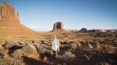 nativo : woman walking in Monument Valley with red rocks overview.