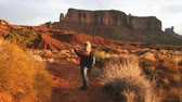 nativo : woman walking in Monument Valley taking photos with smartphone.