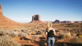ocidental : woman standing in Monument Valley with red rocks overview.