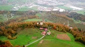 Aerial: Going towards small country farm with castle ruins in background. Flying on early autumn morning sunrise over Slovenian countryside. Stock Footage