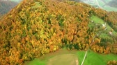 Aerial: Flying over hills with beautiful colorful forests and small farms. Flying on early autumn morning sunrise over Slovenian countryside. Stock Footage