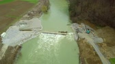 Aerial: Flying towards bridge construction site with river overflowing. Snow melting caused river to rise and flow over bridge construction site. Stock Footage