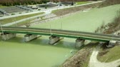 Aerial: Filming old iron railway bridge crossing medium size river. Water filtration plant in background. Stock Footage