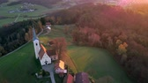 overview : Aerial: Flying around small church on top of small hill. Filming beautiful Slovenian country landscape at autumn early morning. Stock Footage