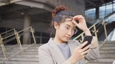 Women play smart phones with friends outside the office building