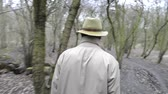 aimless : Man,  wearing a khaki trench coat and a faded felt hat walking through damp,  grey woods