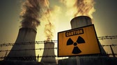 z��pad slunce : Nuclear power plant caution sign and barbed wire mounted at the foot of three large tall cement chimneys exhausting smoke and fumes into the atmosphere, Sunset.