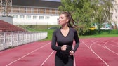 tory : Slim sweaty woman running on athletic field Wideo
