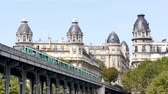 rivet : In Paris, the bir-hakeim bridge crosses the Seine, near the Eiffel Tower. Close-ups of the buildings between which the subway arrives. Metros leave and arrive at Passy station, in the 16th arrondissement.