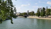 seine : Paris, France, summer. From the island of St. Louis, there is a view over the city hall of the capital, the St. James tower, the towns theater and the river, the Seine. People are passing over a bridge.