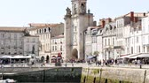 new aquitaine : City center of La Rochelle, a seaport on the Atlantic coast in western France. Its a street near the old port. Filmed during the summer. The clock tower is a gate to the old city.