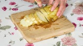 patlıcan : Cutting an eggplant on a wooden board in a kitchen. Theres a table with flowers on the table. Stok Video