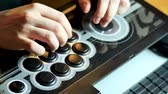 A person is playing a video game with an arcade stick. One hand on the joystick and one on the buttons.