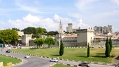 avignon : The Papal Palace is a historical palace located in Avignon, southern France. It is one of the largest and most important medieval Gothic buildings in Europe. Cars are passing in front of it.