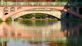 Reflection of two bridges on the water of the river, around the big island in Strasbourg, in the east of France. Filmed in October 2018.
