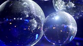 dreamy : Rotating Mirrorballs in a club reflecting blue light - close up shot