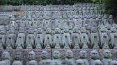 буддист : Small praying monk statues at Hase Dera Temple in Kamakura - TOKYO  JAPAN - JUNE 12, 2018 Стоковые видеозаписи