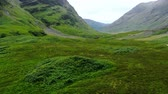 çayır : Glencoe valley in the highlands of Scotland - aerial drone footage Stok Video