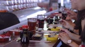 essstäbchen : People eating Sushi in a Running Sushi restaurant Stock Footage