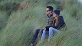 kerry : Young couple enjoys the sound of the ocean while sitting in reed grass