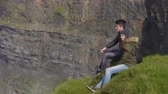 Couple enjoys the view over the Cliffs of Moher in Ireland