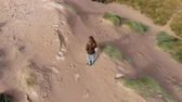 kerry : Aerial view over a girl standing on the top of sand dunes at the coast