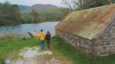 kerry : Two young people walk to a beautiful lake