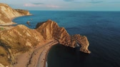 overlooking : Famous Durdle Door in Devon at the British coast at sunset Stock Footage