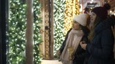 urbane : Two girls in New York look at Christmas decorated shop windows