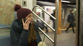 urbane : Young woman takes a phone call in New York subway train