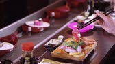 tuňák : Eating Sushi with chopsticks in a Asian restaurant - close up shot Dostupné videozáznamy
