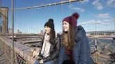 manzana : Two girls walk over the famous Brooklyn Bridge in New York