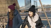 táxi : Two girls walk over the famous Brooklyn Bridge in New York