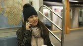 Нью Йорк : Young woman takes a phone call in a New York subway train Стоковые видеозаписи