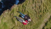 irlandês : Two girls lying in the grass at the cliffs of the Irish coast - drone view from above