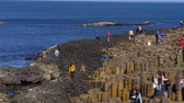 basalto : People climb on the rocks of the famous Giants Causeway in Northern Ireland - BUSHMILLS. NORTHERN IRELAND - MAY 12, 2019 Stock Footage