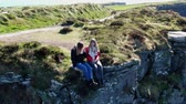 castello : Two girls sit on the edge of the famous Cliffs of Moher in Ireland Filmati Stock