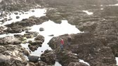 dramático : Two girls in Ireland climb over the rocky oceanfront of Malin Head
