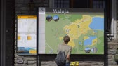 Tourist checks the map of Maloja in Switzerland - SWISS ALPS, SWITZERLAND - JULY 20, 2019