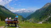 スイス : People enjoy the breathtaking view over the Swiss Alps - SWISS ALPS, SWITZERLAND - JULY 20, 2019