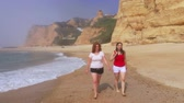 portugália : Running on a sandy beach in Portugal - two girls on holiday Stock mozgókép