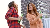 спуск : Young asian woman lesbian couple dancing and clinking bottles of beer party on rooftop.