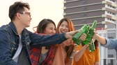 veranda : Group of Asian young people clinking bottles of beer party on rooftop.