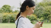Beautiful asian young woman shot surfing the net online. Using mobile phone send text messaging at public park. Stock Footage