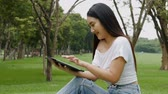 Asian young woman hands using ipad tablet touchscreen at public park. Slow motion filmed. Stock Footage