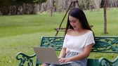 Young asian woman using laptop at public park. Sitting on a bench in a public park. Slow motion filmed.
