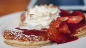 Close up pancake with strawberries, whip cream at cafe.