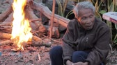 por que : CHIANGRAI, THAILAND - DECEMBER 20: unidentified old asian man sitting in front of campfire because of cold weather on December 20, 2014 in Chiangrai, Thailand.