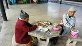 inferno : CHIANG RAI, THAILAND - NOVEMBER 24 : unidentified asian old man and old woman having breakfast on stone bench chair on November 24, 2016 in Chiang rai, Thailand.